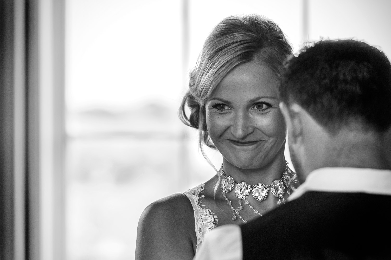 Proud bride smiling during cermeony by Sussex documentary wedding photographer James Robertshaw