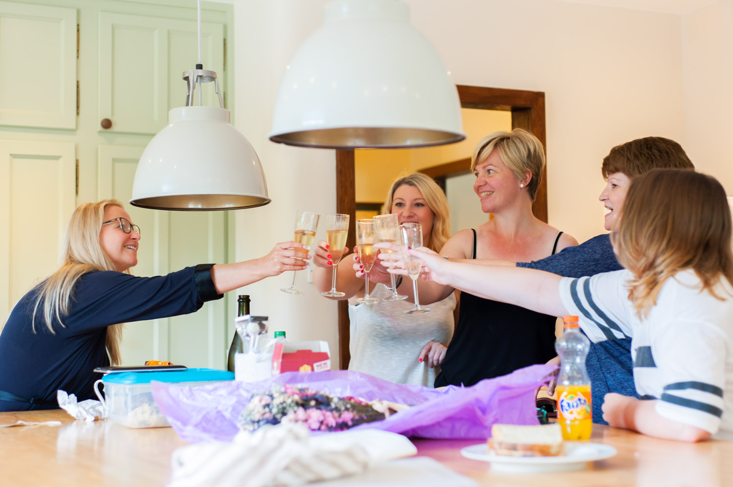 Bride and friends with drinks in kitchen on wedding morning by Sussex documentary wedding photographer James Robertshaw