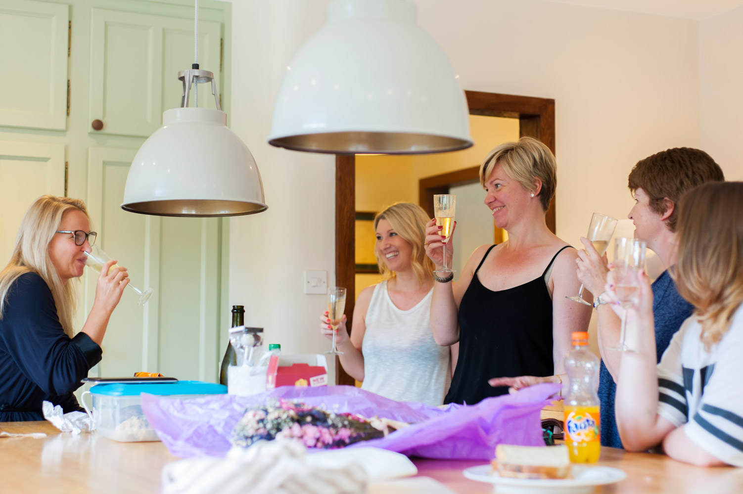 Bride and friends with drinks in kitchen on wedding morning