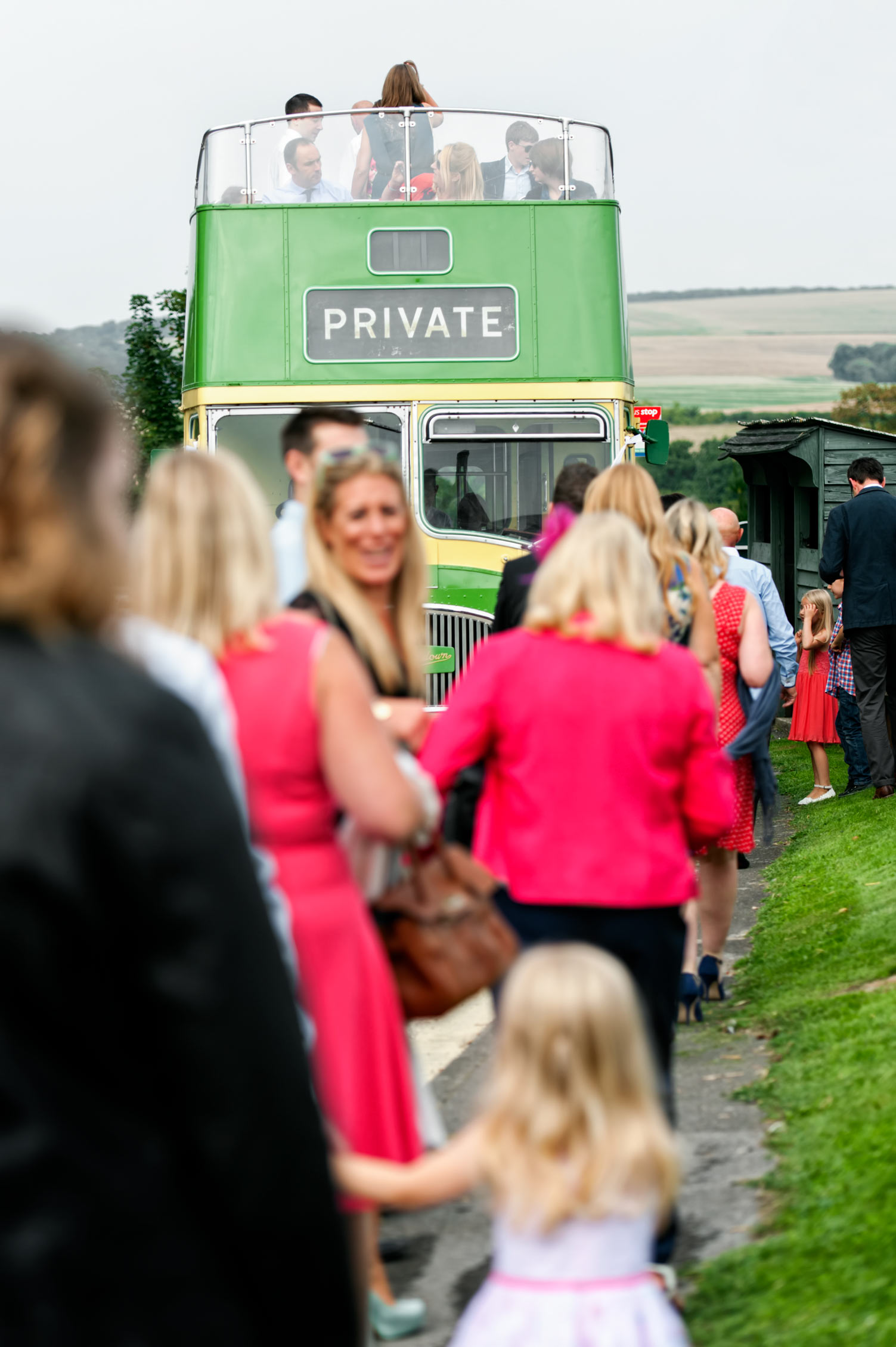 Guests boarding open air wedding bus by Sussex documentary photographer James Robertshaw