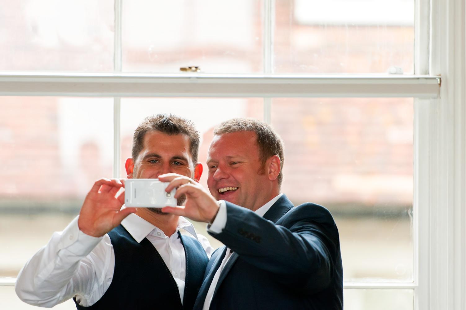 Groom and friend taking selfie