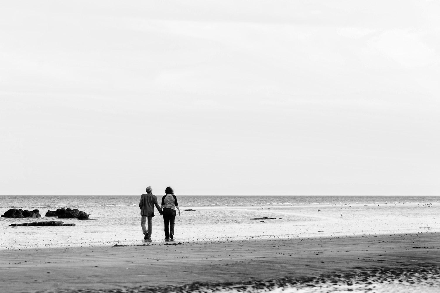 Couple walking on Hastings beach